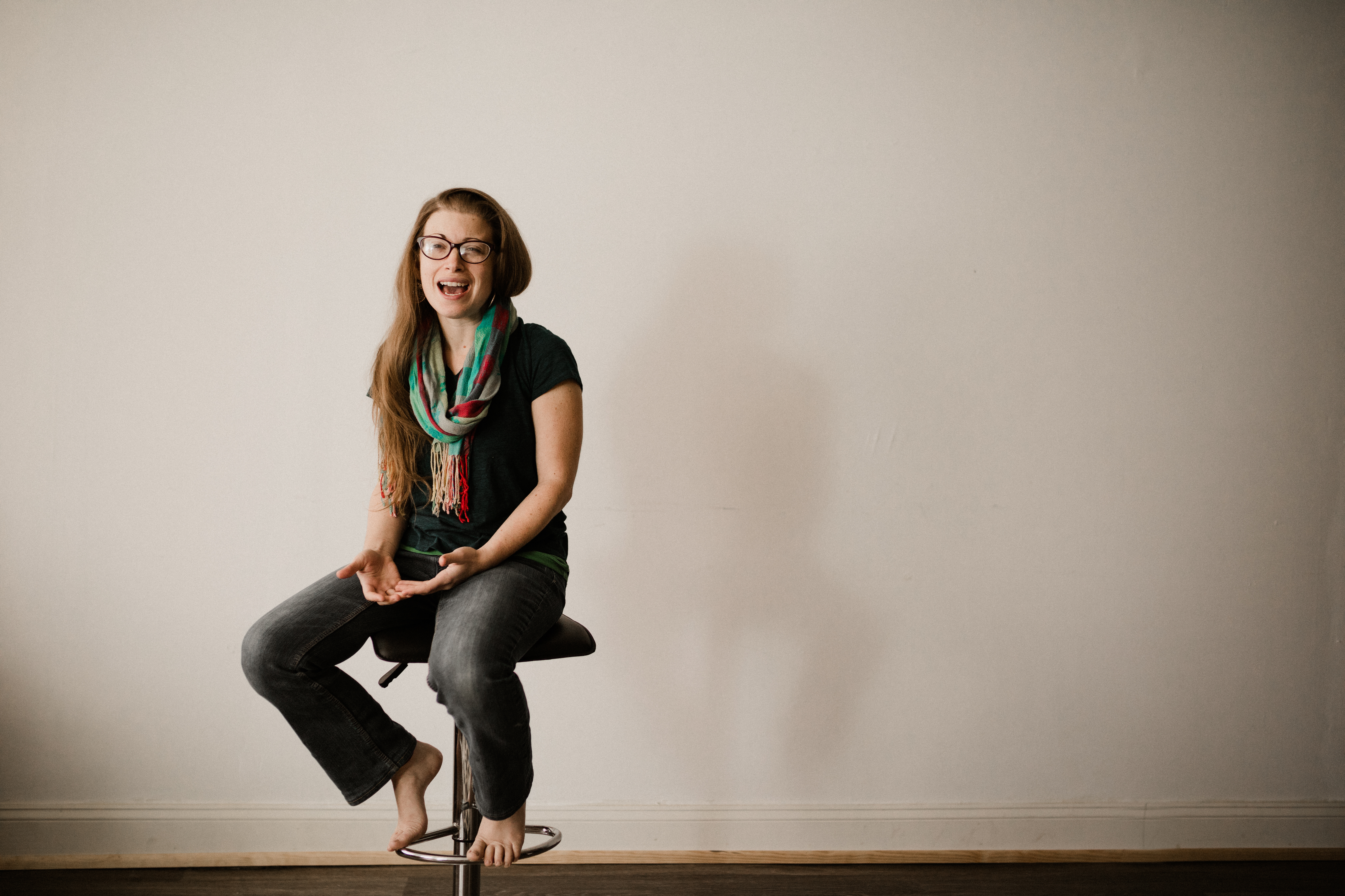 image of Jessie with green and red scarf, black t-shirt and blue jeans sitting on a stool barefoot.