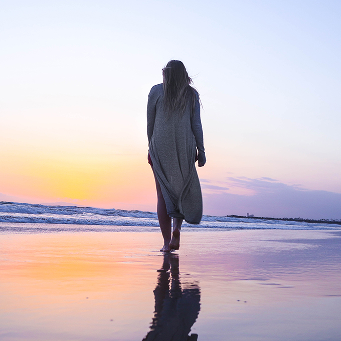 woman walking along beach to symbolize fertility journey